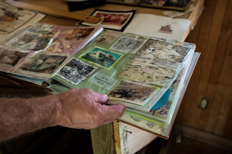 Gary Puett looks through a childhood photo album that was damaged in the flooding from Harvey. (Joseph Rushmore for HuffPost)