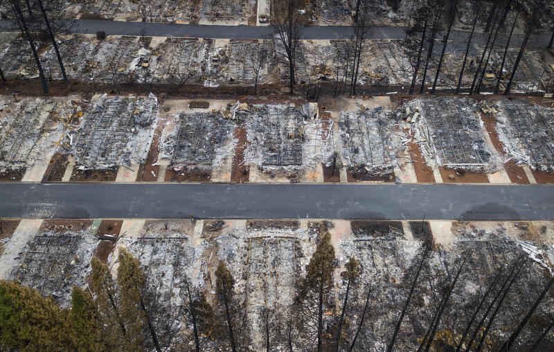 FILE- This Dec. 3, 2018, file photo shows homes leveled by the Camp Fire line the Ridgewood Mobile Home Park retirement community in Paradise, Calif. Insurance claims from California's deadly November 2018 wildfires have topped $11.4 billion. State Insurance Commissioner Ricardo Lara said Monday, Jan. 28, 2019, that more than $8 billion worth of damage comes from the fire that leveled the town of Paradise and killed 86 people. About $3 billion more is from two Southern California wildfires that ignited the same week. (AP Photo/Noah Berger, File)