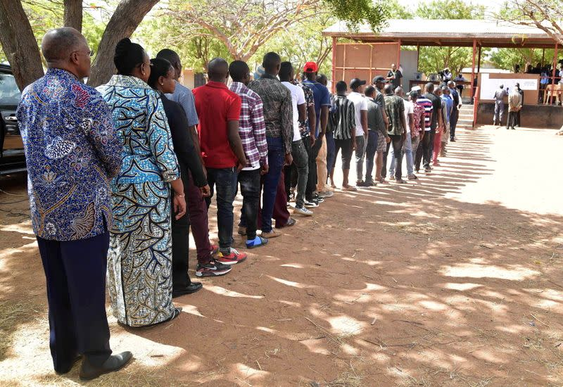 Tanzanian President John Pombe Magufuli and First Lady Janeth stand in the queue before casting their ballots at a polling centre during the Presidential and Parliamentary elections in Chamwino district in Dodoma