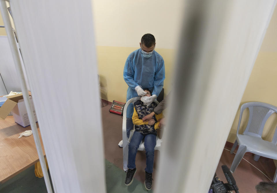 A health care worker takes a nasal swab sample from a Palestinian child at a COVID-19 testing center, in the Palestine Medical Complex, in the West Bank city of Ramallah, Tuesday, March 2, 2021. (AP Photo/Nasser Nasser)
