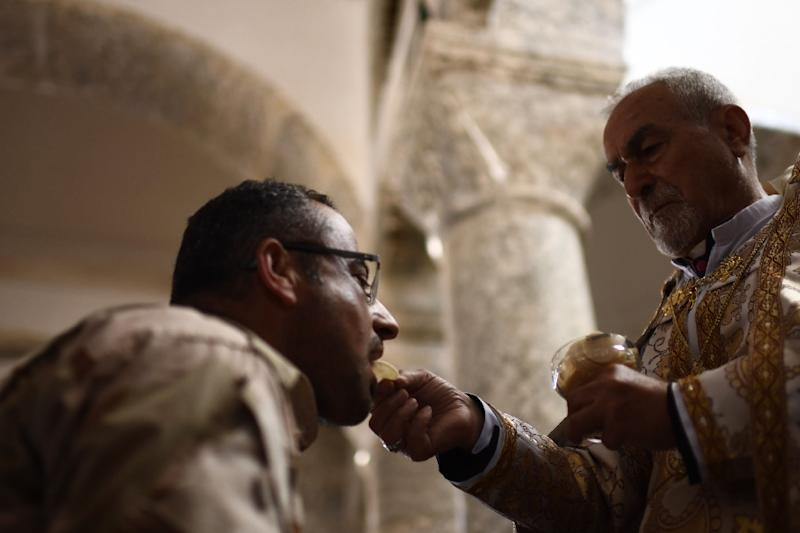 A priest gives the Eucharist during Easter mass at the Mar Yohanna church in the Christian Iraqi town of Qaraqosh on April 16, 2017 (AFP Photo/CHRISTOPHE SIMON)