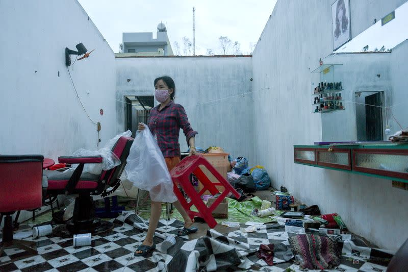 A woman works in a barbershop damaged by the Typhoon Molave in Binh Chau village