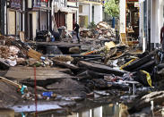A man carries debris out of a house in Bad Muenstereifel, western Germany, Sunday, July 18, 2021. Heavy rains caused mudslides and flooding in the western part of Germany. Multiple have died and are missing as severe flooding in Germany and Belgium turned streams and streets into raging, debris-filled torrents that swept away cars and toppled houses. (Oliver Berg/dpa via AP)