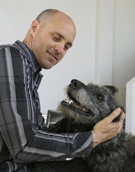 Martin Sprouse with 'Grady', an Airedale Terrier-Irish Wolfhound mix, Thursday, April 18, 2013, in Oakland, Calif. After his owner brought the dog to the Kauai Humane Society because he was moving, the dog with the big brown eyes languished for four months, said shelter operations manager Brandy Varvel. But now Grady is living in a spacious California loft with a new owner who is admittedly smitten thanks to an arrangement the Kauai Humane Society has with the East Bay SPCA in Oakland. The Kauai Humane Society has been reaching out since December to Hawaii tourists willing to bring a little extra baggage, one of the island's many strays and abandoned dogs, when returning to the Bay Area. The dogs are mostly mixed breeds derived from Airedales, whippets and hounds; breeds which are used in the Hawaii Islands to hunt feral pigs. (AP Photo/Ben Margot)