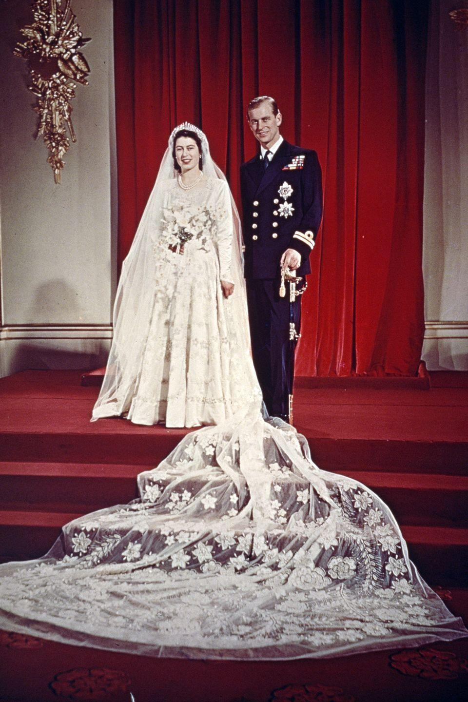 <p>The Queen rocked an elegant wedding dress with a 13-foot bridal trail designed by Norman Hartnel.</p>