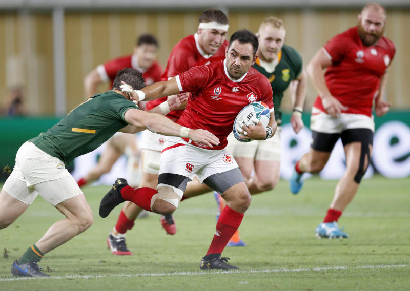 Canada's Phil Mack attempts to run past a South African defender during the Rugby World Cup Pool B game at Kobe Misaki Stadium between South Africa and Canada in Kobe, Japan, Tuesday, Oct. 8, 2019. (Kyodo News via AP)