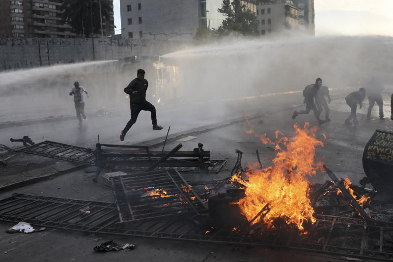 Anti-government protesters run from police spraying water cannons where a street barricade burns, set by demonstrators, in Santiago, Chile, Tuesday, Oct. 29, 2019. Chileans gathered Tuesday for a 12th day of demonstrations that began with youth protests over a subway fare hike and have become a national movement demanding greater socio-economic equality and better public services in a country long seen as an economic success story. (AP Photo/Rodrigo Abd)