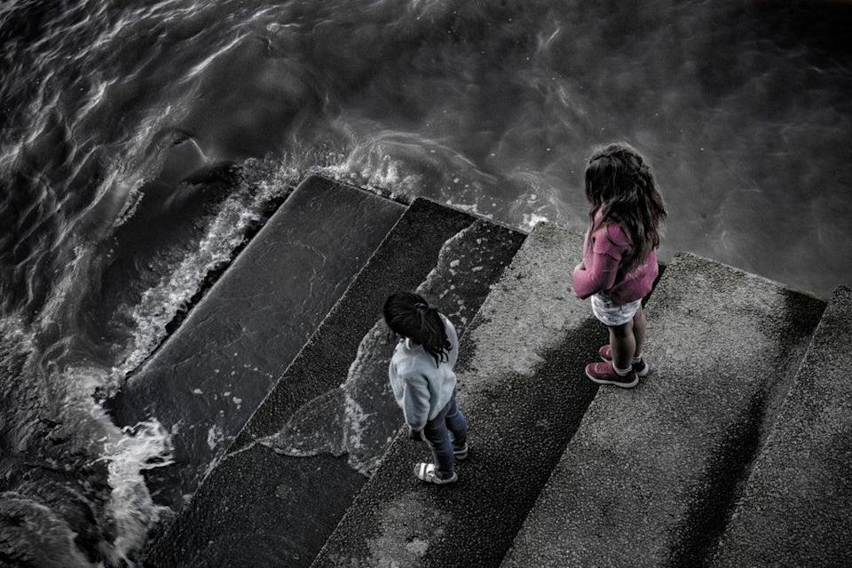 Elizabeth, six, left, and Mali, eight, watch the tide coming in on the Thames; as global sea levels rise, cities on coasts and tidal rivers will be first to feel the effects of increased flooding and will take the worst of the impacts (Britta Jaschinski/WWF-UK)