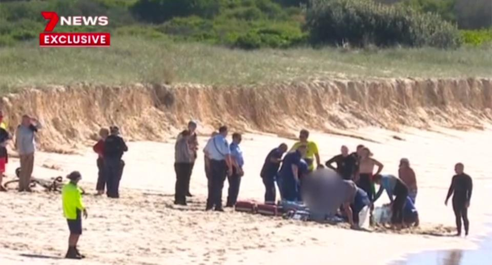 Beachgoers and police surround a shark attack victim on Tuncurry beach.