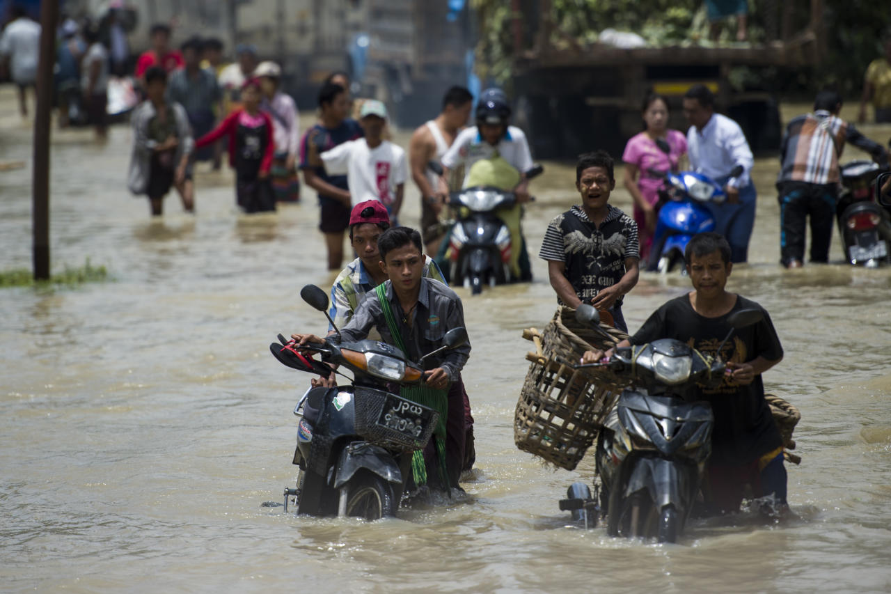 <p>Residents make their way through a flooded road in Taungnu township of Bago region in Myanmar on Aug. 31, 2018. (Photo: Ye Aung THU/AFP/Getty Images) </p>
