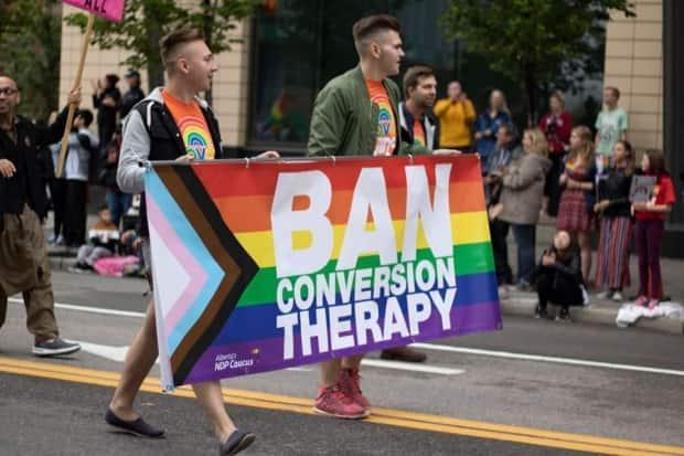 Participants in Calgary's 2019 Pride parade carried banners calling for conversion therapy to be banned. (Michaela Neuman Photography - image credit)