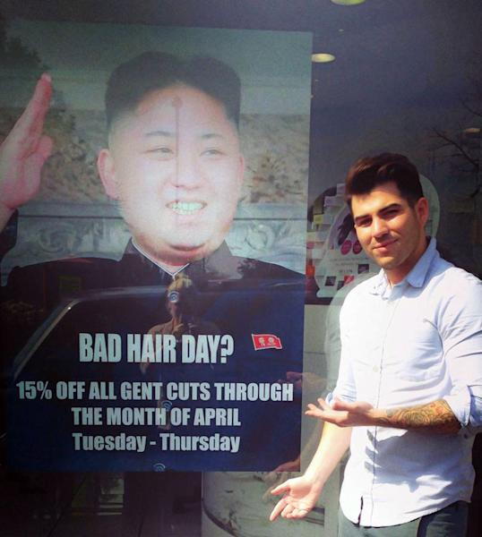 """This undated photo provided by M&M Hair Academy in South Ealing, west London, shows barber Karim Nabbach standing next to a poster poking fun at North Korean leader Kim Jong-un unusual hairstyle. North Korean diplomats have asked the British government take action against a London hair salon's poster poking fun at distinctively coiffured leader Kim Jong Un. The Foreign Office said Wednesday it had received a letter from the country's embassy objecting to the poster, and was considering its response. The Evening Standard newspaper reported that the letter urged Britain to take """"necessary action to stop the provocation."""" Staff at M&M Hair Academy say they were visited by diplomats from the nearby embassy after putting up a poster featuring a picture of Kim - who sports a distinctive undercut - and the slogan """"Bad Hair Day?"""" Police say they spoke to both parties and determined no crime had been committed. The embassy didn't immediately respond to a request for comment. (AP Photo/M&M Hair Academy)"""