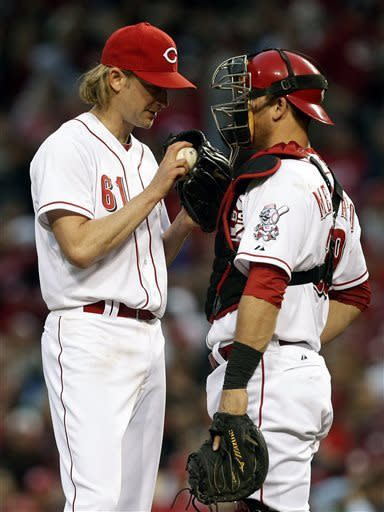 Cincinnati Reds starting pitcher Bronson Arroyo (61) talks with catcher Devin Mesoraco in the fourth inning of a baseball game against the Atlanta Braves, Monday, May 6, 2013, in Cincinnati. (AP Photo/Al Behrman)