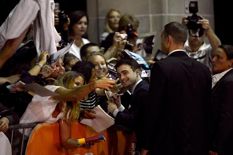 """Daniel Radcliffe signs autographs as he arrives at the premiere of """"The F Word"""" on day 3 of the Toronto International Film Festival at the Ryerson Theatre on Saturday, Sept. 7, 2013, in Toronto. (Photo by Chris Pizzello/Invision/AP)"""