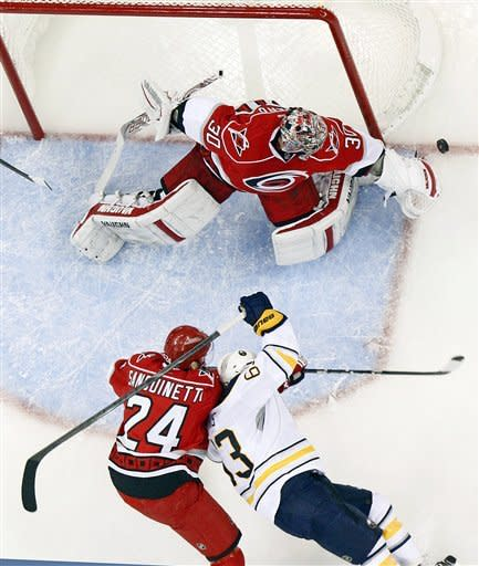Carolina Hurricanes' Cam Ward (30) gathers in the puck in front of a charging Buffalo Sabres' Tyler Ennis (63) and Hurricanes' Bobby Sanguinetti (24) during the second period of an NHL hockey game in Raleigh, N.C., Thursday, Jan. 24, 2013. (AP Photo/Karl B DeBlaker)