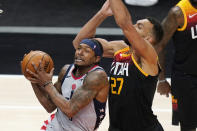 Washington Wizards guard Bradley Beal, left, goes to the basket as Utah Jazz center Rudy Gobert (27) defends in the first half during an NBA basketball game Monday, April 12, 2021, in Salt Lake City. (AP Photo/Rick Bowmer)