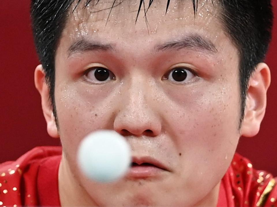 China's Fan Zhendong stares at a ping pong ball in the air at the Tokyo Olympics.