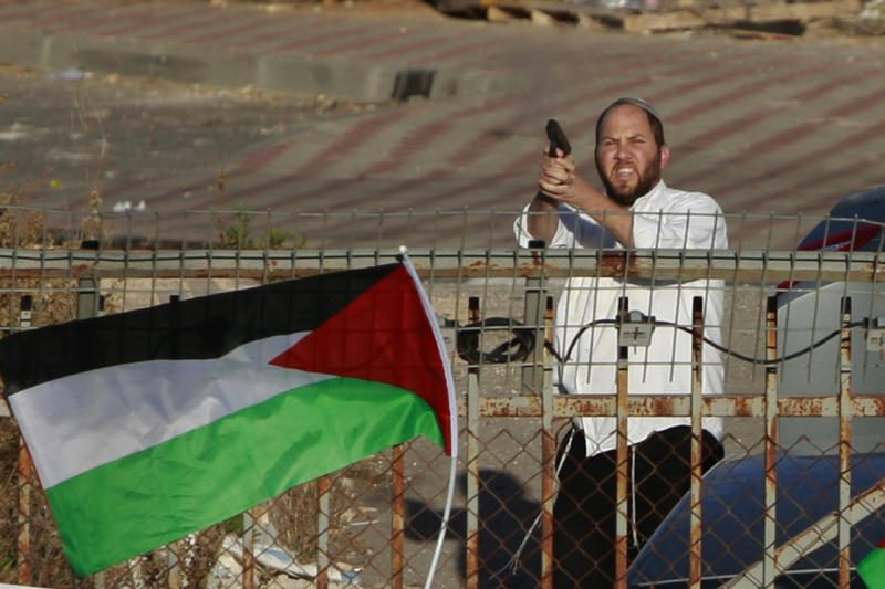 An Israeli Jewish settler shoots in the air as Palestinians protest against the Prawer Plan to resettle Israel's Palestinian Bedouin minority from their villages in the Negev Desert, near the Israeli settlement of Bet El, north of the West Bank city of Ramallah, Saturday, Nov. 30, 2013. (AP Photo/Majdi Mohammed)
