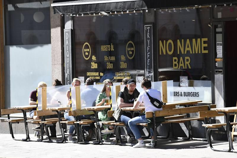 People enjoy the sunny weather at an outdoor restaurant in Stockholm on May 30 amid the novel coronavirus pandemic. Source: AFP