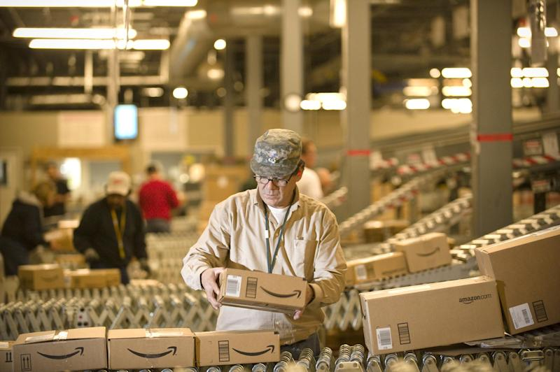 FILE - In this Monday, Dec., 1, 2008, file photo, an Amazon.com employee grabs boxes off the conveyor belt to load in a truck at their Fernley, Nev., warehouse. Cyber Monday, coined in 2005 by a shopping trade group that noticed a spike in online sales on the Monday after Thanksgiving when people returned to their work computers, is the next in a line of days that stores are counting on to jumpstart the holiday shopping season. This year it is expected to be the biggest online shopping day of the year for the third year in a row. (AP Photo/Scott Sady)