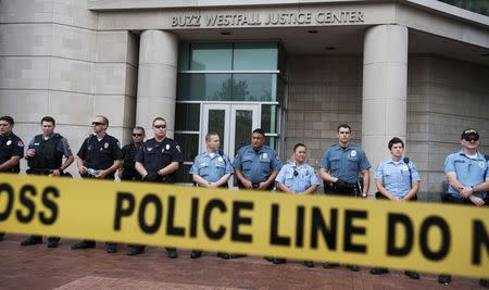 Police guard the entrance to the St. Louis County Justice Building in Clayton, Missouri as protestors gather in the street in this August 20, 2014 file photo. REUTERS/Mark Kauzlarich/Files