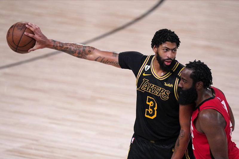 Los Angeles Lakers' Anthony Davis (3) extends his arm with the ball as James Harden defends him during the second half of an NBA conference semifinal playoff basketball game Sunday, Sept. 6, 2020, in Lake Buena Vista, Fla. The Lakers won 117-109.(AP Photo/Mark J. Terrill)