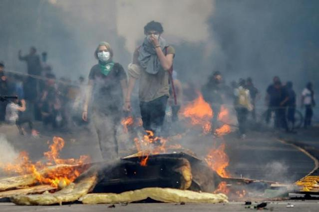 Violent unrest in Santiago has seen metros and buses burned, and clashes between riot police and protesters (AFP Photo/Pablo VERA)