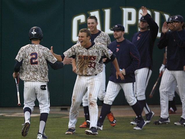 The Pepperdine bench comes out to celebrate a go-ahead run by Hutton Moyer (2) in the seventh inning of an NCAA college baseball tournament regional game against Cal Poly on Saturday, May 31, 2014, in San Luis Obispo, Calif. (AP Photo/Aaron Lambert)