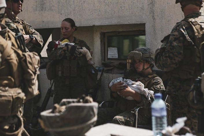 Marines assigned to the 24th Marine Expeditionary Unit (MEU) calm infants during an evacuation at Hamid Karzai International Airport, Kabul, Afghanistan, Aug. 20