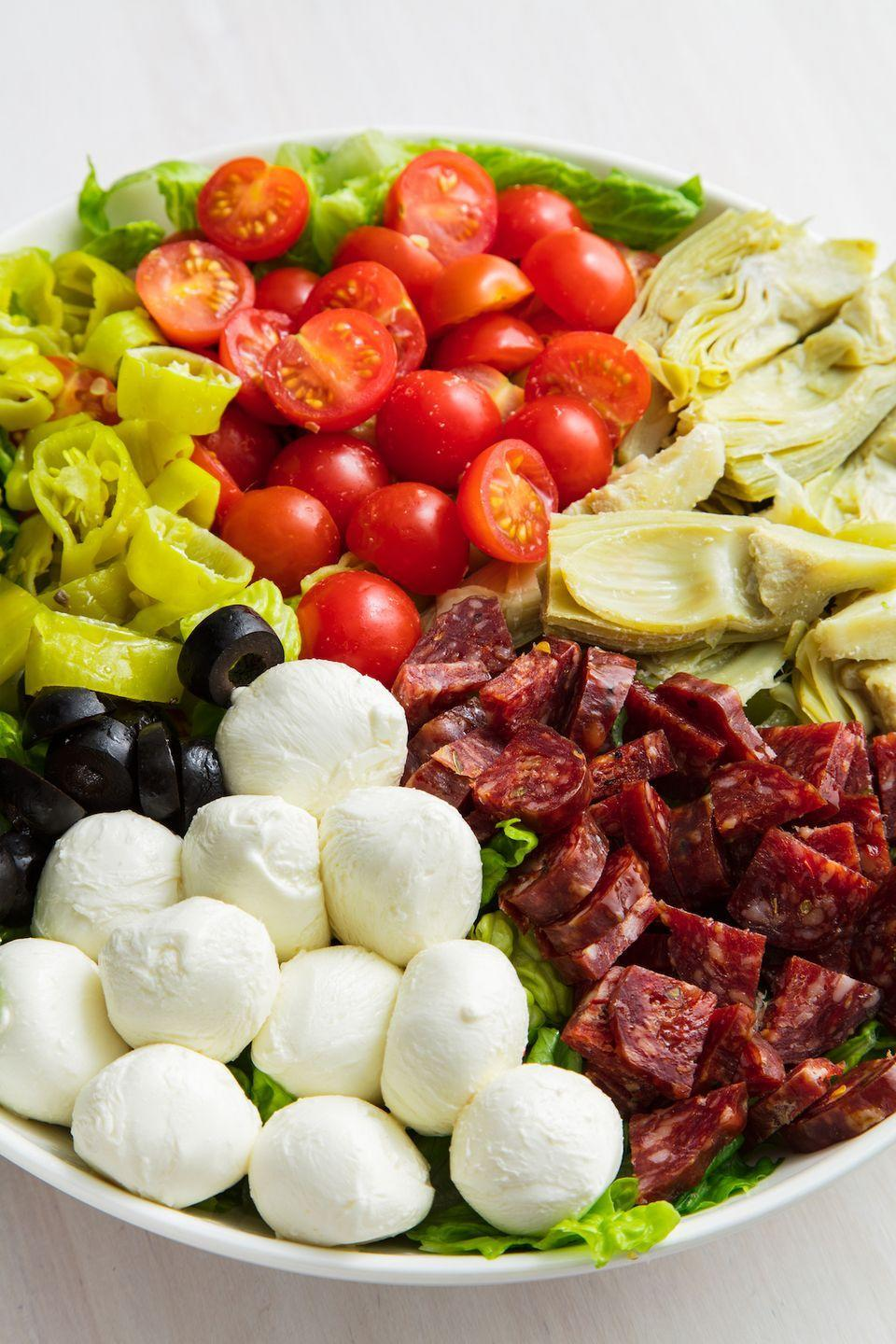"""<p>Gang's all here: tomatoes, artichoke hearts, salami, mozz balls, and pepperoncini make for the best salad EVER.</p><p>Get the recipe from <a href=""""https://www.delish.com/cooking/recipe-ideas/a19885331/antipasto-salad-recipe/"""" rel=""""nofollow noopener"""" target=""""_blank"""" data-ylk=""""slk:Delish"""" class=""""link rapid-noclick-resp"""">Delish</a>. </p>"""