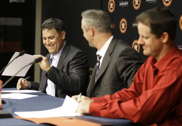 Former Houston Astros players Lance Berkman, left, and Roy Oswalt, right, sign one-day service contracts as club president Reid Ryan looks on during a news conference before a baseball game against the Los Angeles Angels, Saturday, April 5, 2014, in Houston. Berkman and Oswalt signed the contracts so they could retire as Astros. (AP Photo/Pat Sullivan)