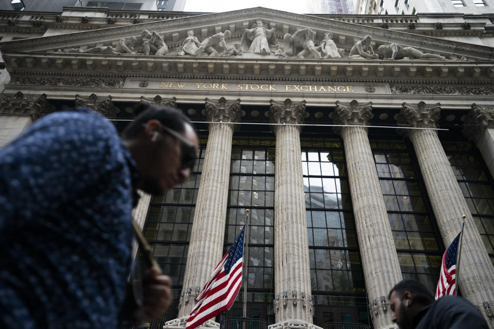 Pedestrians pass the New York Stock Exchange, Monday, Oct. 4, 2021, in New York. U.S. stocks are opening mixed on Friday, Oct. 8, after a disappointing jobs report thudded onto Wall Street and raised questions about whether the Federal Reserve will change its timeline to pare back its support for markets.(AP Photo/John Minchillo)