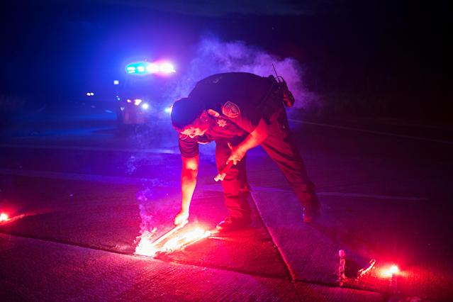 <p>A police officer lays down a safety flare while blocking the road leading to the Arkema SA plant which was hit by floods caused Tropical Storm Harvey near Crosby, Texas, Aug. 31, 2017. (Photo: Adrees Latif/Reuters) </p>