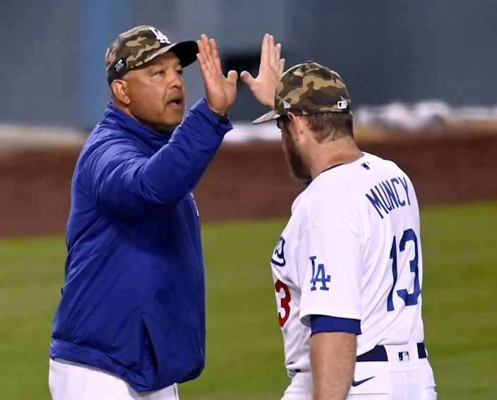 Dodgers manager Dave Roberts, left, high-fives with first baseman Max Muncy.