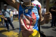 A woman wears a T-shirt with the image of Venezuelan opposition leader Henrique Capriles as people gather for a demonstration against President Nicolas Maduro in Caracas, Venezuela, Saturday, April 8, 2017. Capriles was banned from running for office for 15 years. Opponents of President Nicolas Maduro are preparing to flood the streets of Caracas on Saturday as part of a week-long protest movement that shows little sign of losing steam. (AP Photo/Ariana Cubillos)
