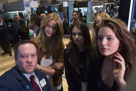 Goldman Sachs Specialist trader Michael Shearin speaks with 2014 Sports Illustrated Swimsuit Models Kate Bock, Emily Ratajkowski, Gigi Hadid and Emily DiDonato (L-R) on the floor of the New York Stock Exchange February 13, 2014. REUTERS/Brendan McDermid