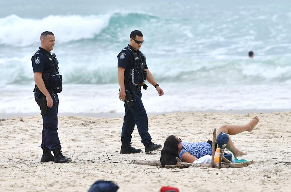 Police are seen moving on a sunbather from the beach at Burleigh Heads on the Gold Coast on Friday. Source: AAP