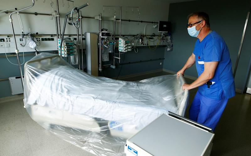 A member of the medical staff prepares a room reserved for patients suffering from the coronavirus disease (COVID-19) in an intensive care unit at St.-Antonius-Hospital in Eschweiler, Germany - REUTERS