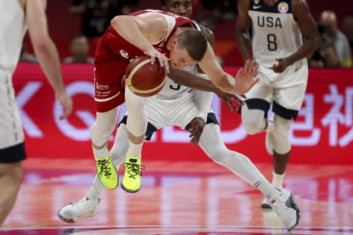 Poland's Adam Waczynski fights for the ball against United States' Donovan Mitchell during a consolation playoff game for the FIBA Basketball World Cup at the Cadillac Arena in Beijing on Saturday, Sept. 14, 2019. U.S. defeated Poland 87-74 (AP Photo/Ng Han Guan)