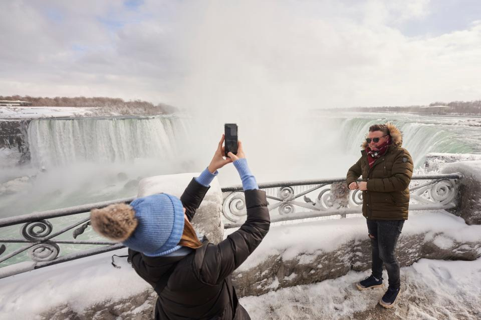 A man has his photo taken at the Horseshoe Falls in Niagara Falls, Ontario, on January 27, 2021. (Photo by Geoff Robins / AFP) (Photo by GEOFF ROBINS/AFP via Getty Images)
