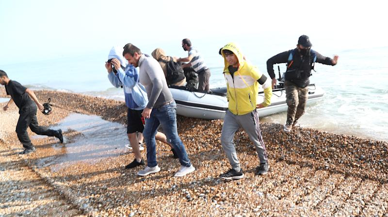 A group of people thought to be migrants run from an inflatable boat at Kingsdown beach, near Dover, Kent, where they arrived after crossing the English Channel.
