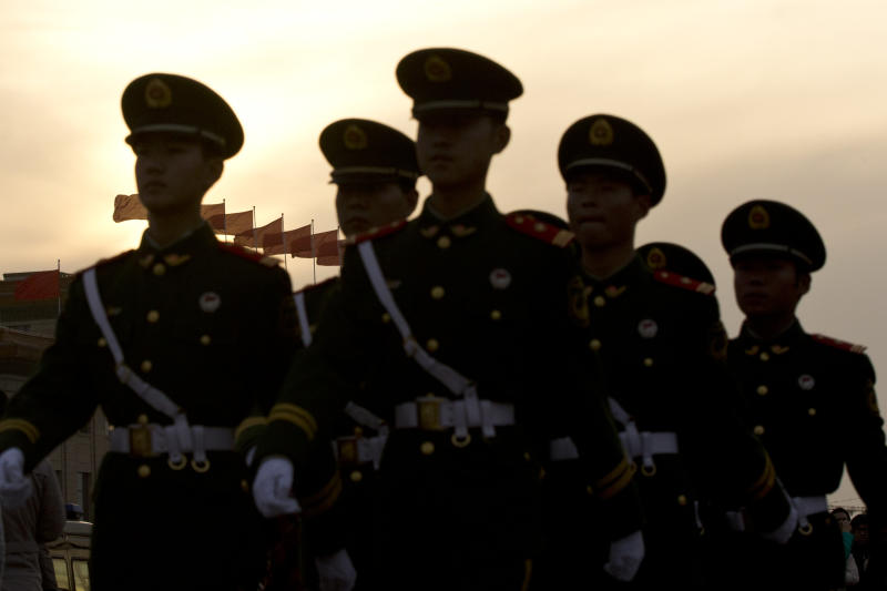 Paramilitary policemen patrol Wednesday, Nov. 7, 2012, in front of Tiananmen Gate, near the Great Hall of the People where the Chinese Communist Party's 18th National Congress begins Thursday in Beijing. The once-a-decade event installs a new leadership to run the world's second largest economy and newly assertive global power. (AP Photo/Alexander F. Yuan)