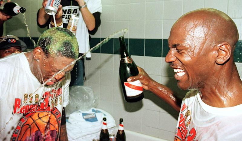 SALT LAKE CITY, UNITED STATES: Dennis Rodman (L) of the Chicago Bulls gets beer and champagne poured on his head by teammate Michael Jordan (R) and others 14 June after winning game six of the NBA Finals against the Utah Jazz at the Delta Center in Salt Lake City, UT. The Bulls won the game 87-86 to take their sixth NBA Championship. AFP PHOTO/Mike NELSON (Photo credit should read MIKE NELSON/AFP via Getty Images)