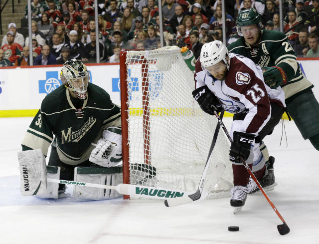 Colorado Avalanche center Maxime Talbot (25) controls the puck past Minnesota Wild defenseman Ryan Suter (20) as Wild goalie Darcy Kuemper (35) covers the net during the second period of Game 4 of an NHL hockey first-round playoff series in St. Paul, Minn., Thursday, April 24, 2014. (AP Photo/Ann Heisenfelt)