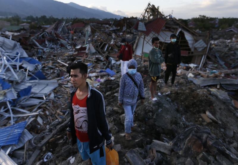 People survey the damage caused by Sept. 28 earthquake at Balaroa neighborhood in Palu, Central Sulawesi, Indonesia, Wednesday, Oct. 10, 2018. Indonesia's disaster agency said Wednesday that it only needs tents, water treatment units, generators and transport from other countries as it responds to the Sulawesi earthquake and tsunami that killed more than 2,000 people. (AP Photo/Dita Alangkara)