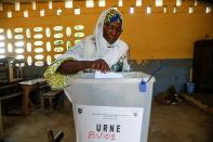 A woman casts her ballot at a polling station during the legislative election in Abidjan