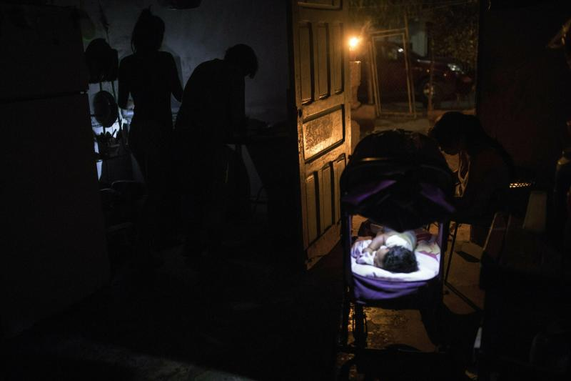 In this May 15, 2019 photo, the Zabala family prepares dinner at their home during a black out in Maracaibo, Venezuela. Venezuela's current President Nicolás Maduro accuses the Trump administration of sabotaging the power grid in a bid to overthrow him and install a puppet government led by opposition politician Juan Guaidó. (AP Photo/Rodrigo Abd)