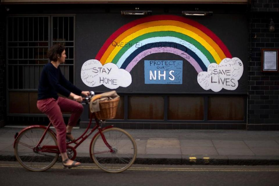 A woman cycles past a rainbow graffiti in support of the NHS in Soho (PA) (PA Archive)