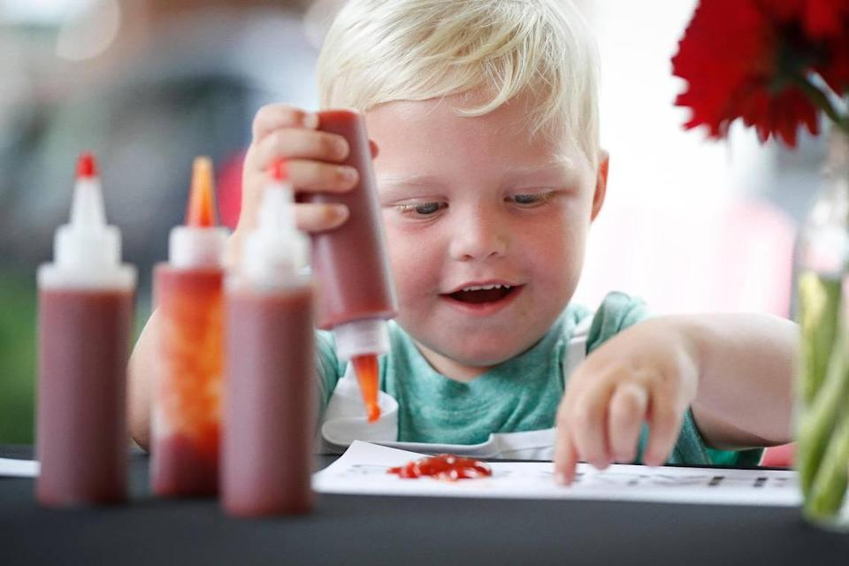 Asher Lawson, 3, of Owensboro, Ky., reacts while finger painting with ketchup during Ketchup Art on the Green at The Summit at Fritz Farm in Lexington, Saturday, July 31, 2021.