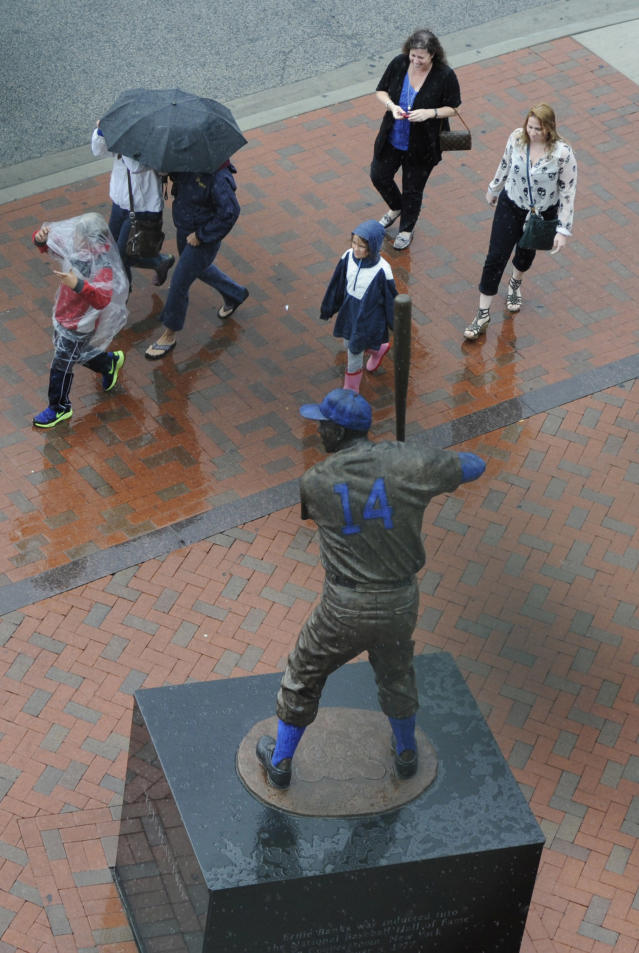 CHICAGO, IL - AUGUST 09: People walk past the Ernie Banks statue during a rain storm before a game between the Chicago Cubs and the Cincinnati Reds on August 9, 2012 at Wrigley Field in Chicago, Illinois. The game has been delayed due to rain. (Photo by David Banks/Getty Images)